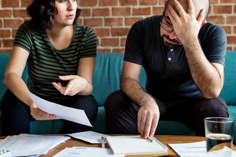 frustrated man and woman sitting on couch looking at paperwork