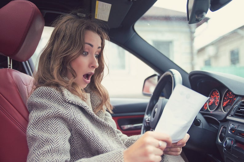 Woman sitting in car looking at piece of paper in shock.