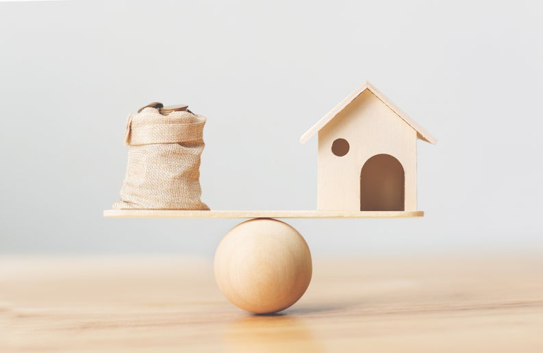 A toy house and a burlap bag of coins on opposite sides of a scale.