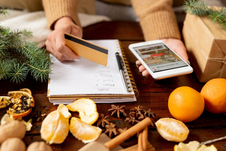 A woman writing a gift list while holding a credit card and phone with oranges and spices on the table in front of her.