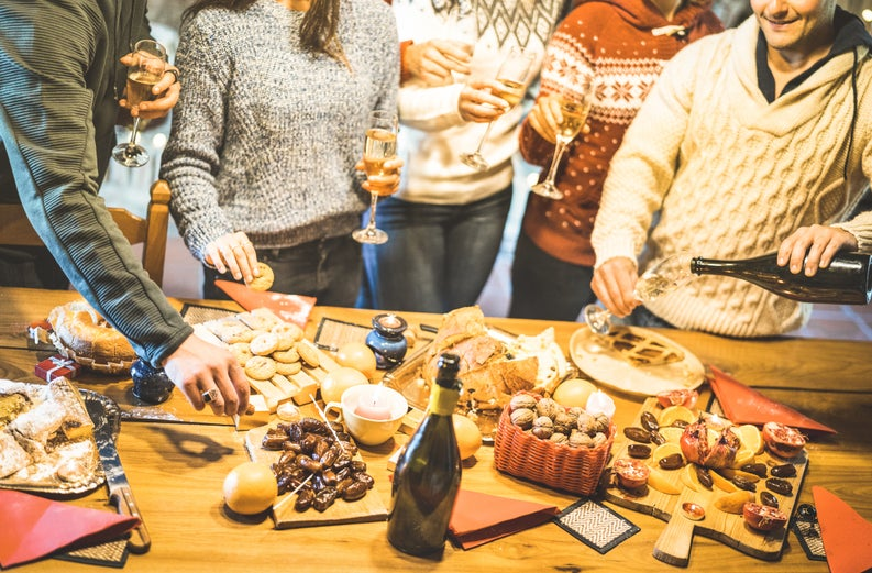A group of friends in holiday sweaters gathered around platters of food and Champagne.
