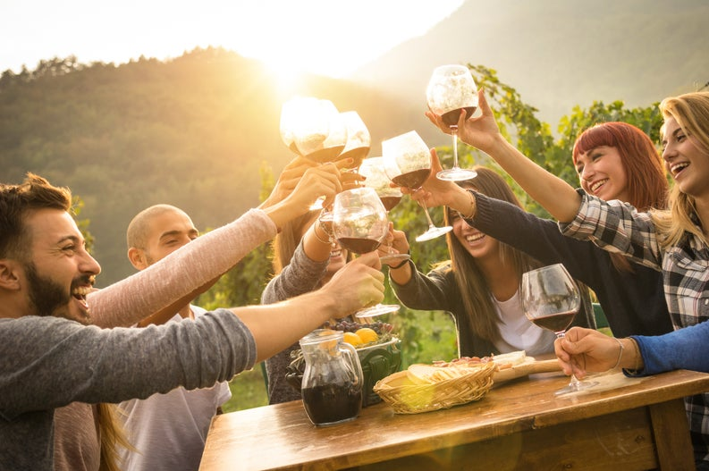 A group of friends clinking their wine glasses together on a sunny patio.