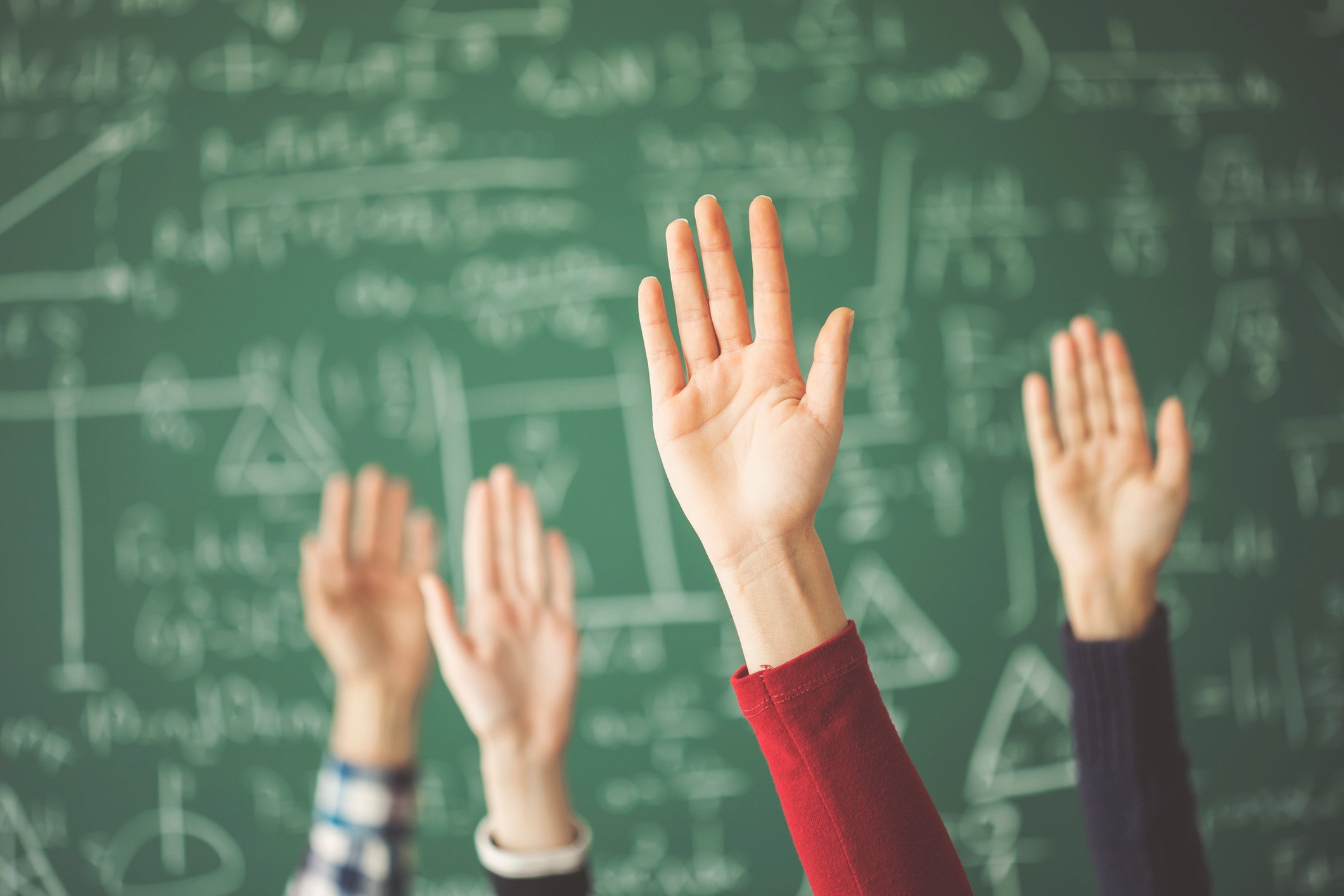 Hands raised in front of a chalkboard.