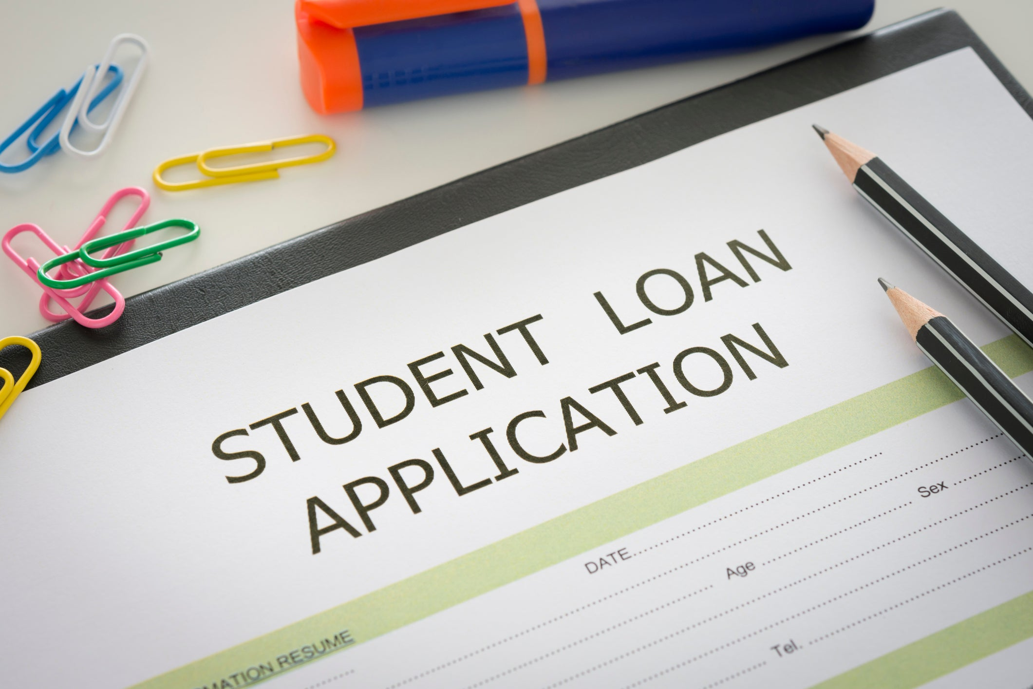 Student loan application with pencils and paperclips on top of it.