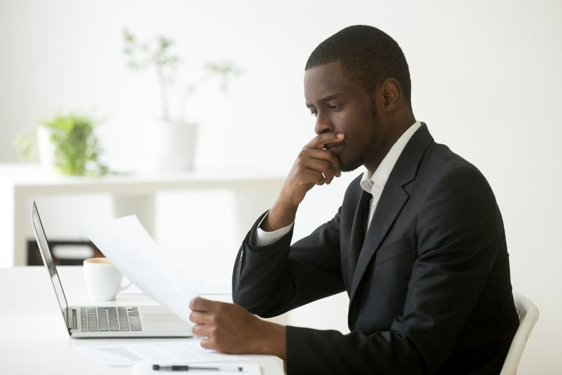 young man pensively mulling over document