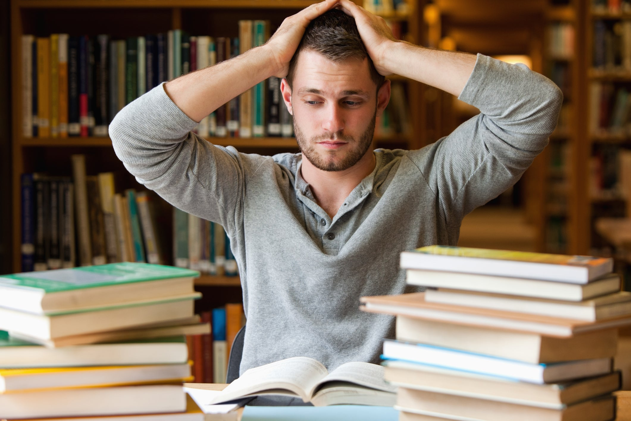 A stressed male college student with a stack of books in the library.