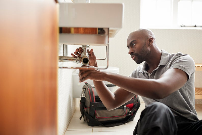 A male plumber fixing the pipes under a sink.