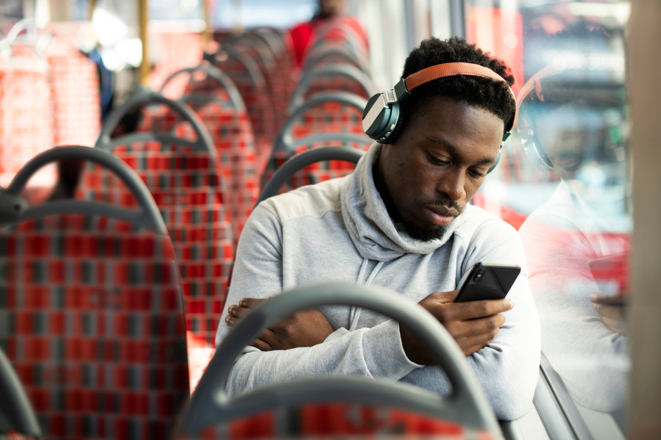 A man riding the bus and listening to music while looking at his phone.
