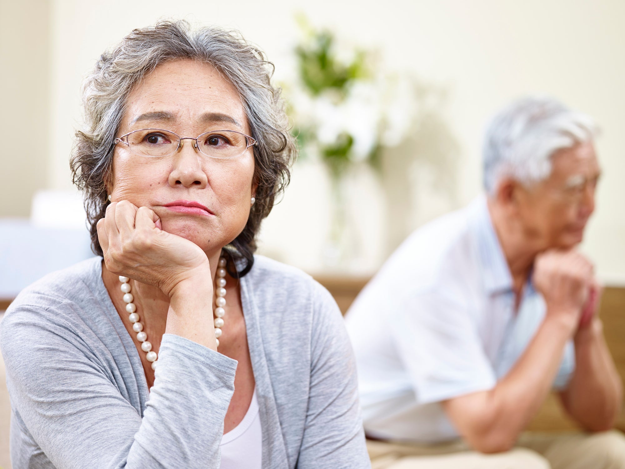 An older couple looking stressed and facing away from each other on a couch.