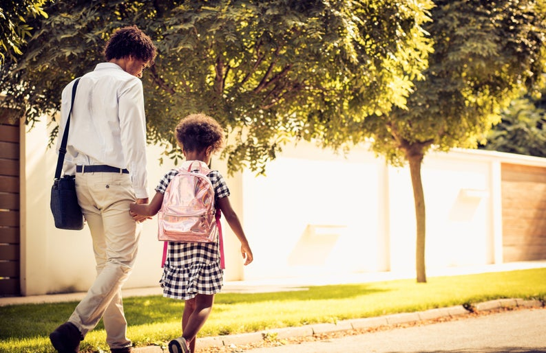 A father walking hand-in-hand with his young daughter wearing a backpack.