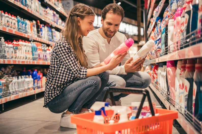 Couple comparing cleaning products in a store aisle.