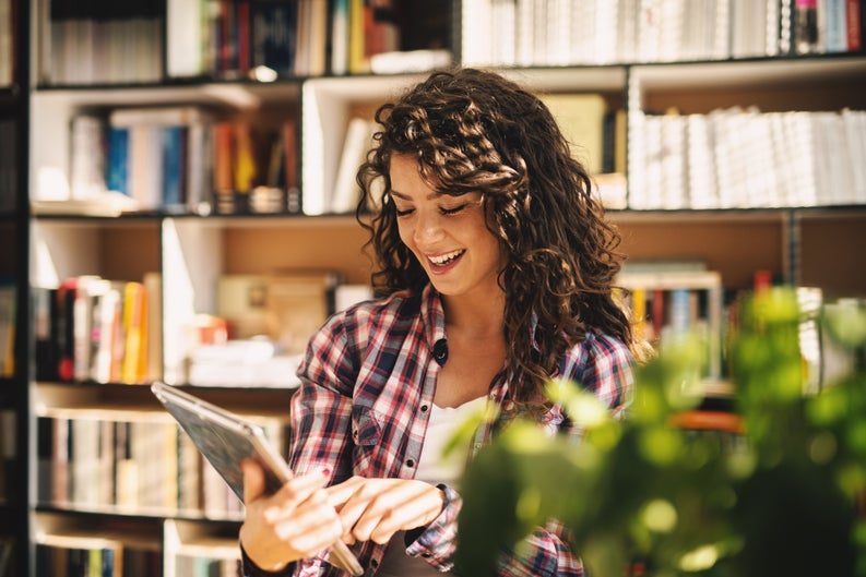 Smiling Young Woman Using Tablet In Library