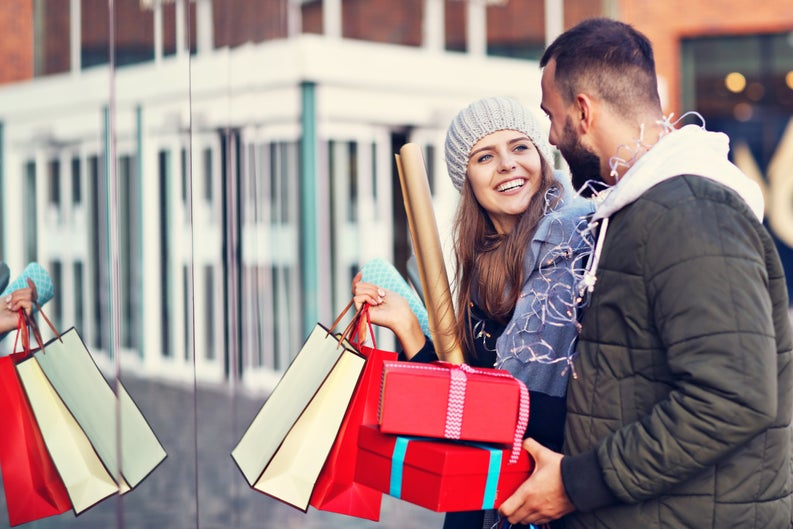 A smiling couple carrying gift-wrapped bags and boxes outside of a store.