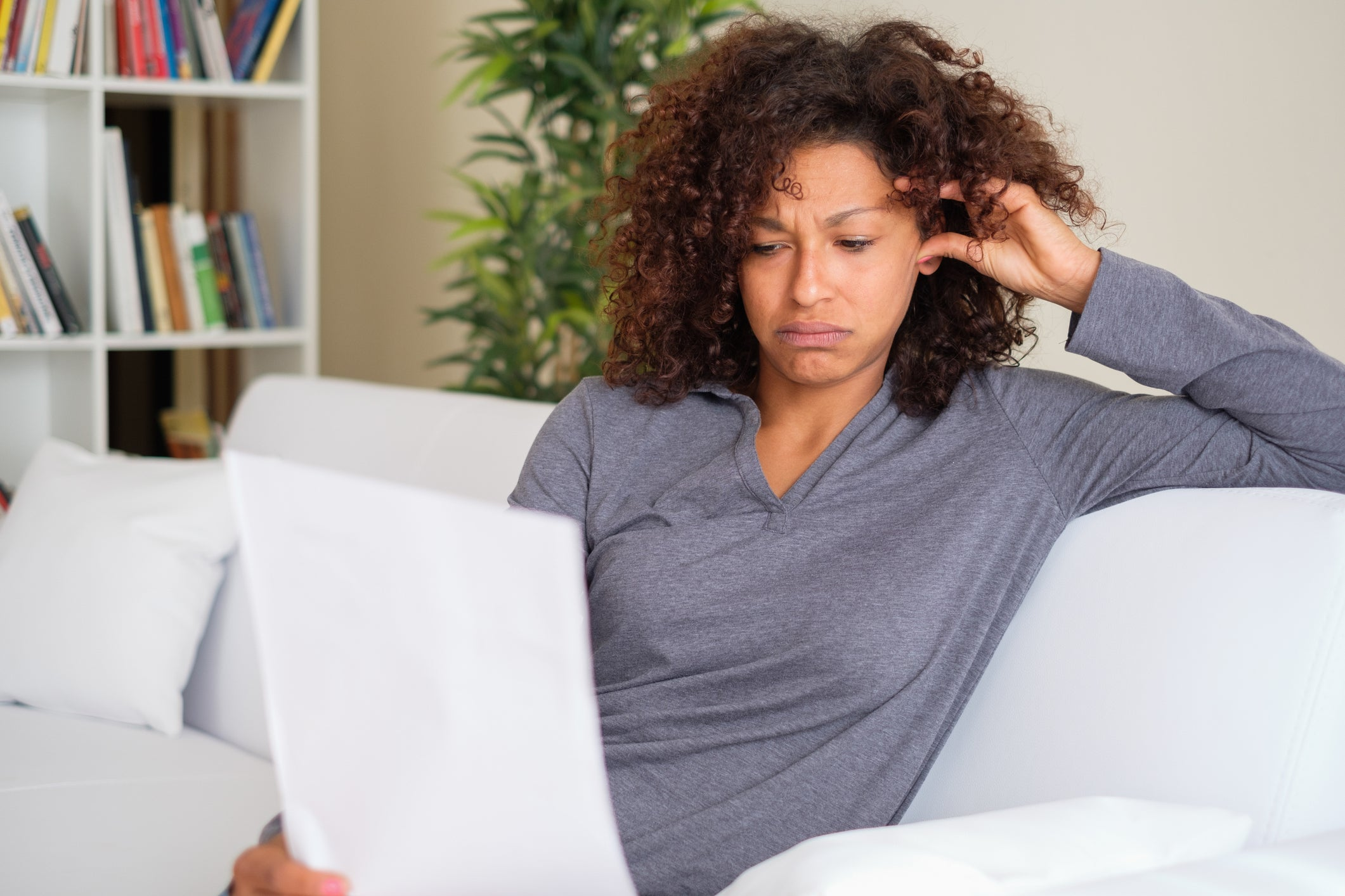 A stressed woman reading paperwork while sitting on her couch.