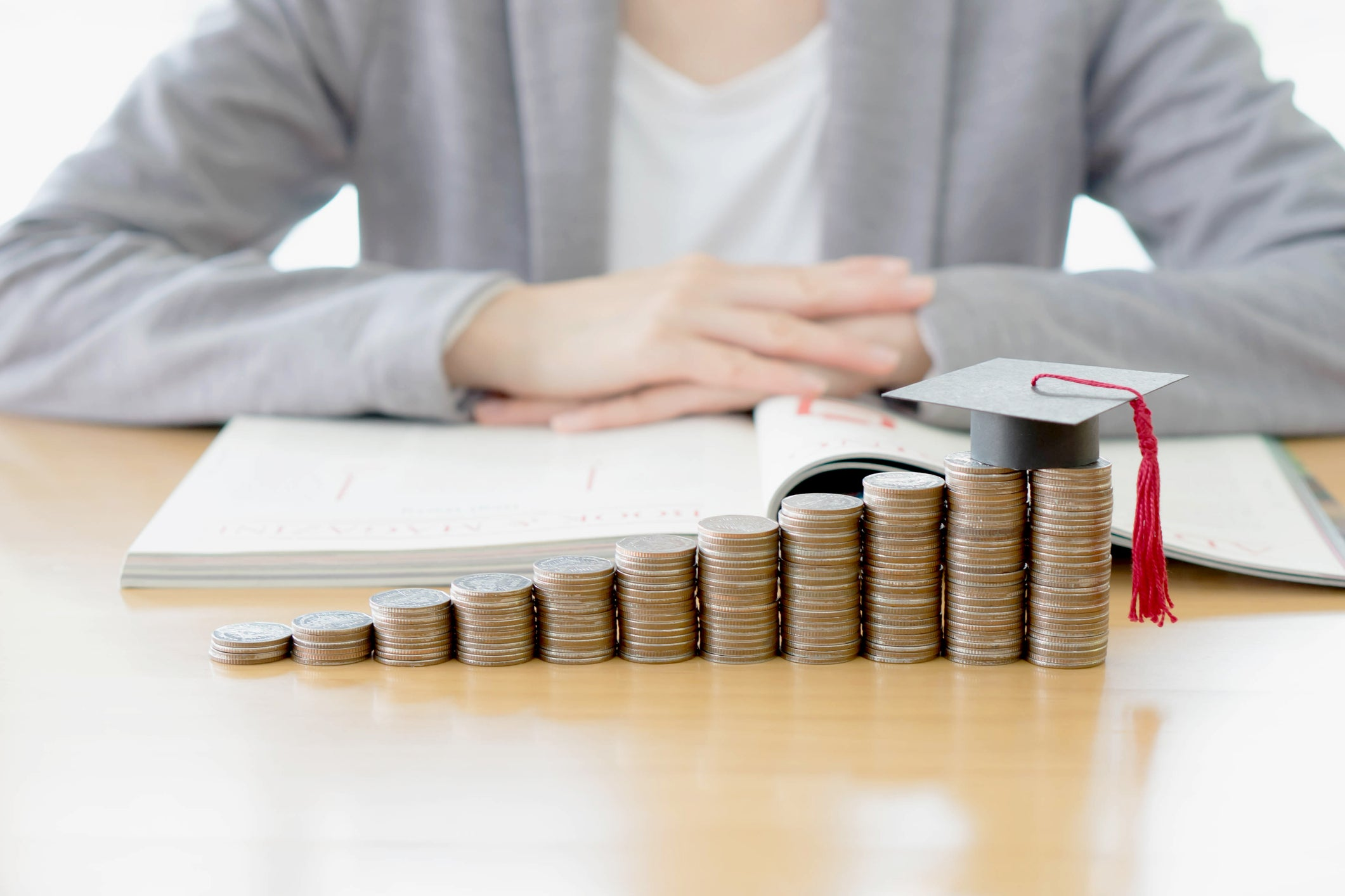 woman sitting behind stacks of coins with a mortarboard on top.