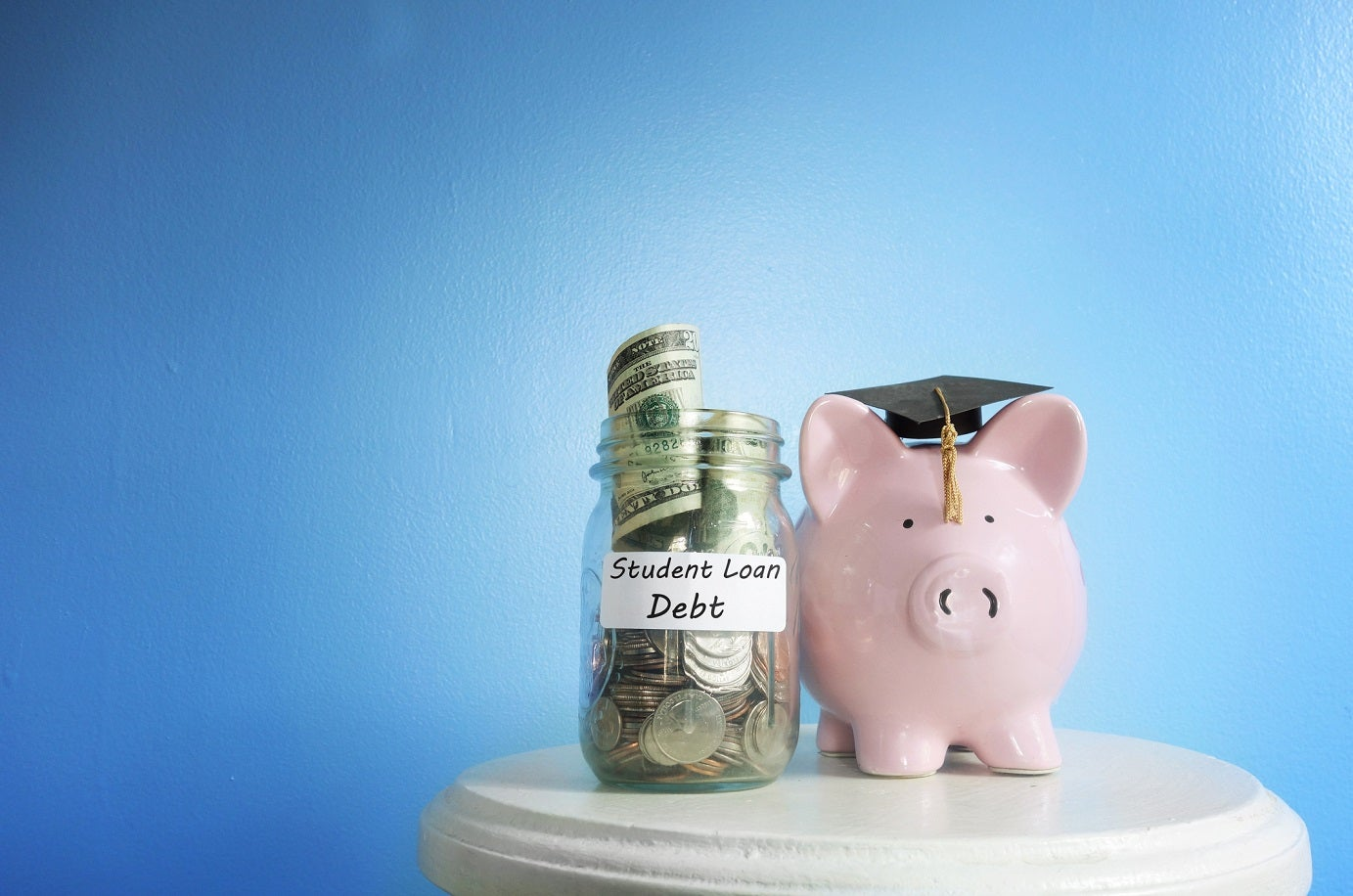 Piggy bank in graduation cap next to a glass jar full of money labeled Student Loan Debt.