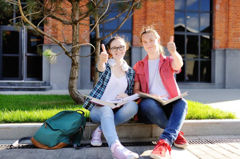 Two students sitting on a curb with books in their laps and giving thumbs up.
