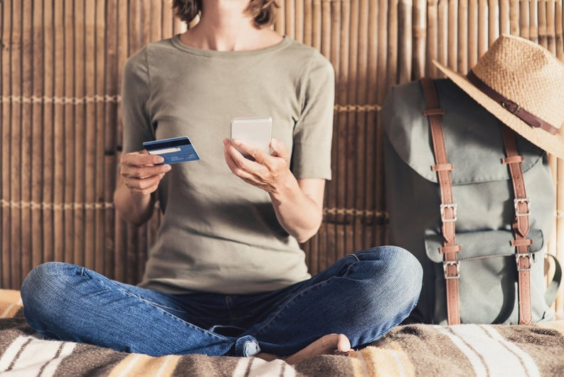 Woman sitting cross legged next to a traveler's backpack holding a phone and a credit card