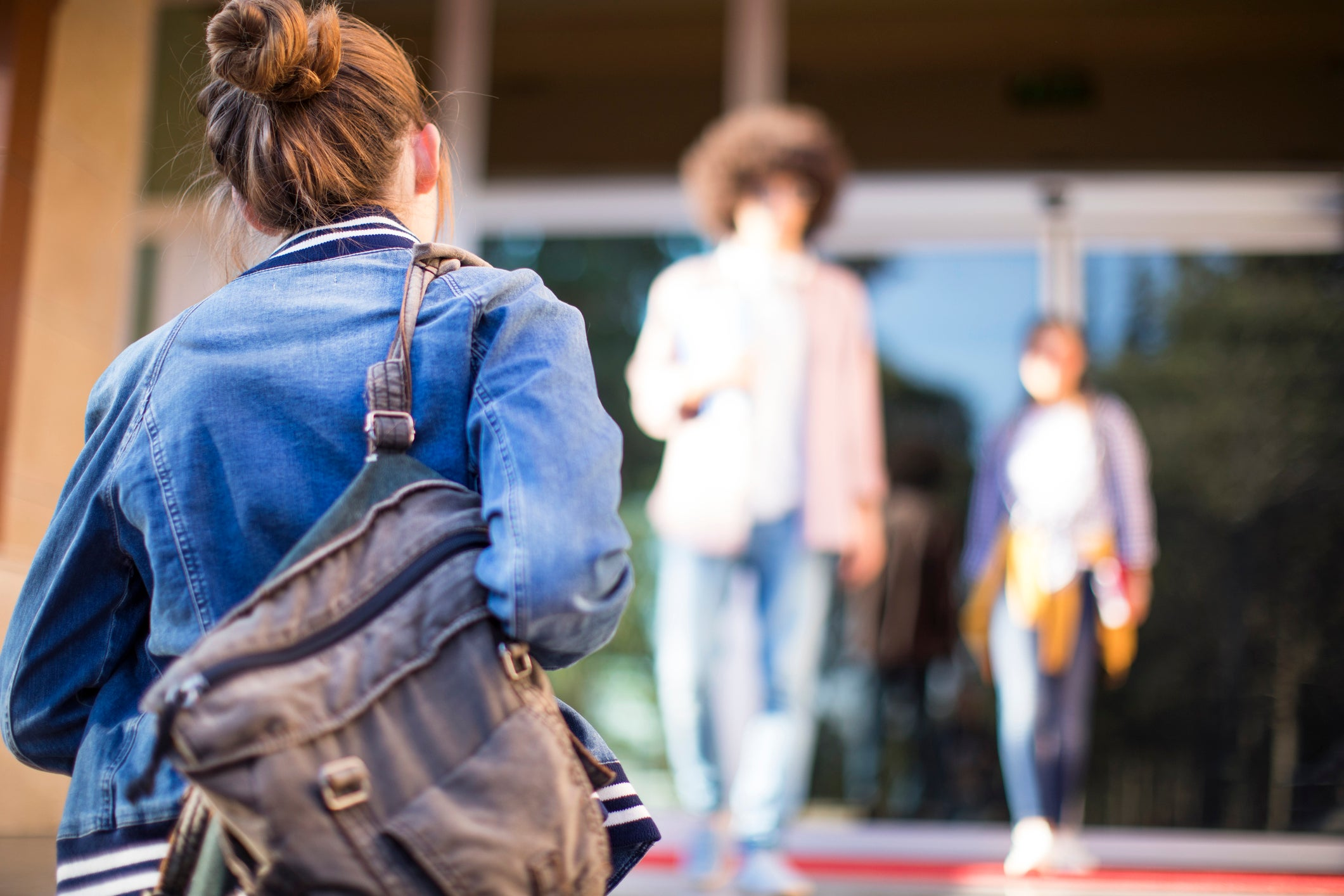 Female Student Walking Into School With Backpack Over Her Shoulder