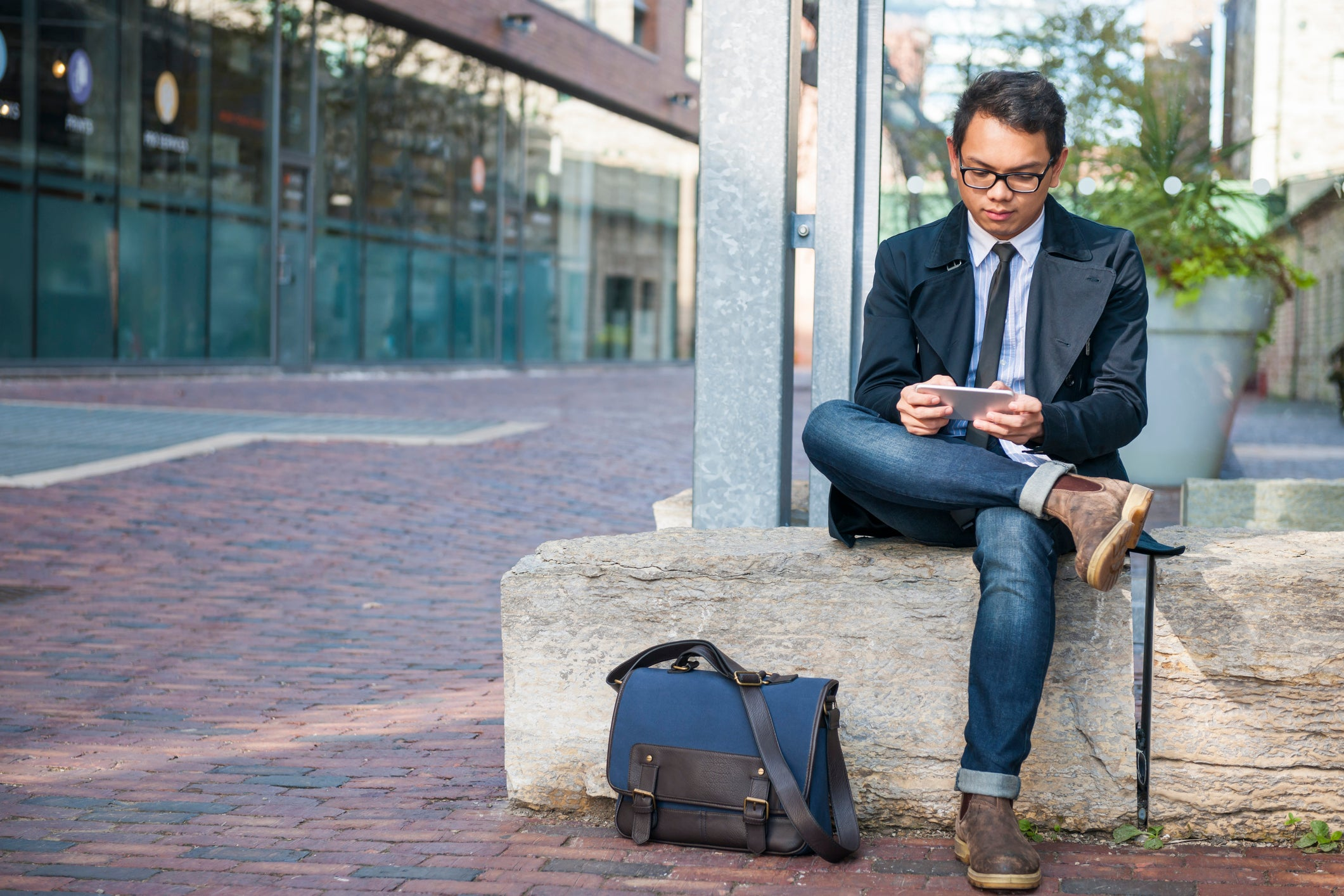 A well-dressed man on sitting on a stone bench and reading something on his phone.