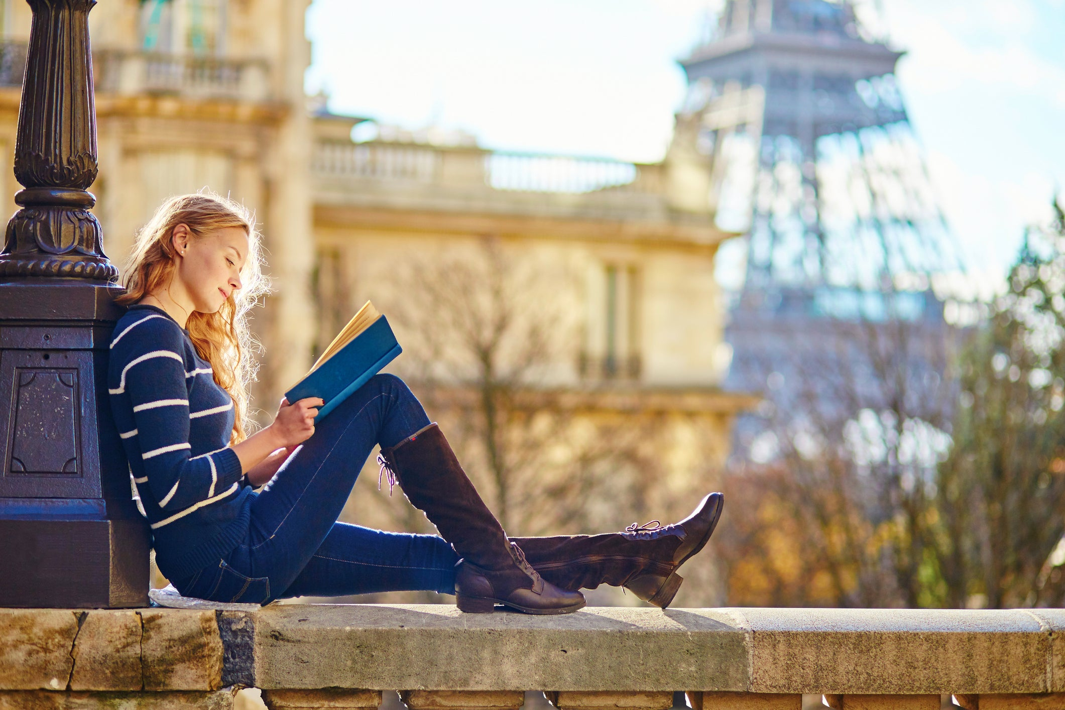 A young woman reading a book with the Eiffel Tower in the background.