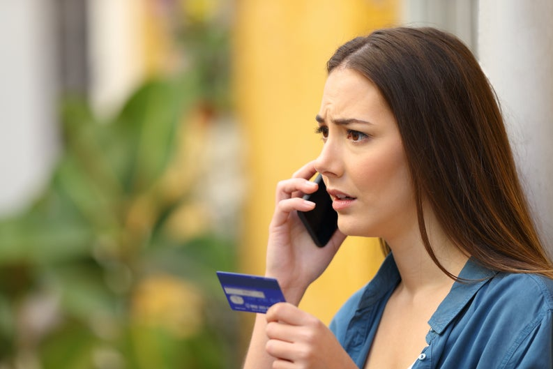 Worried-looking woman on phone holding at prepaid card.