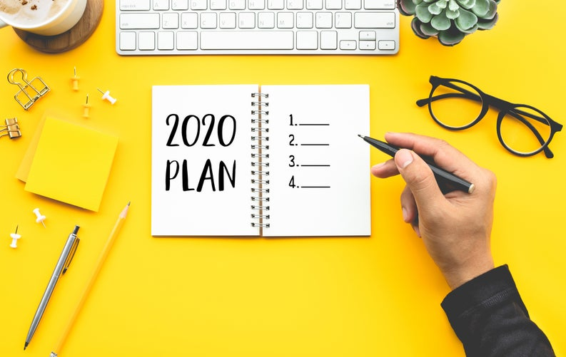 A hand writing in a notebook that says 2020 Plan with glasses and desk items scattered around.