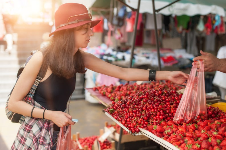 A young woman shopping for strawberries at a farmers market.
