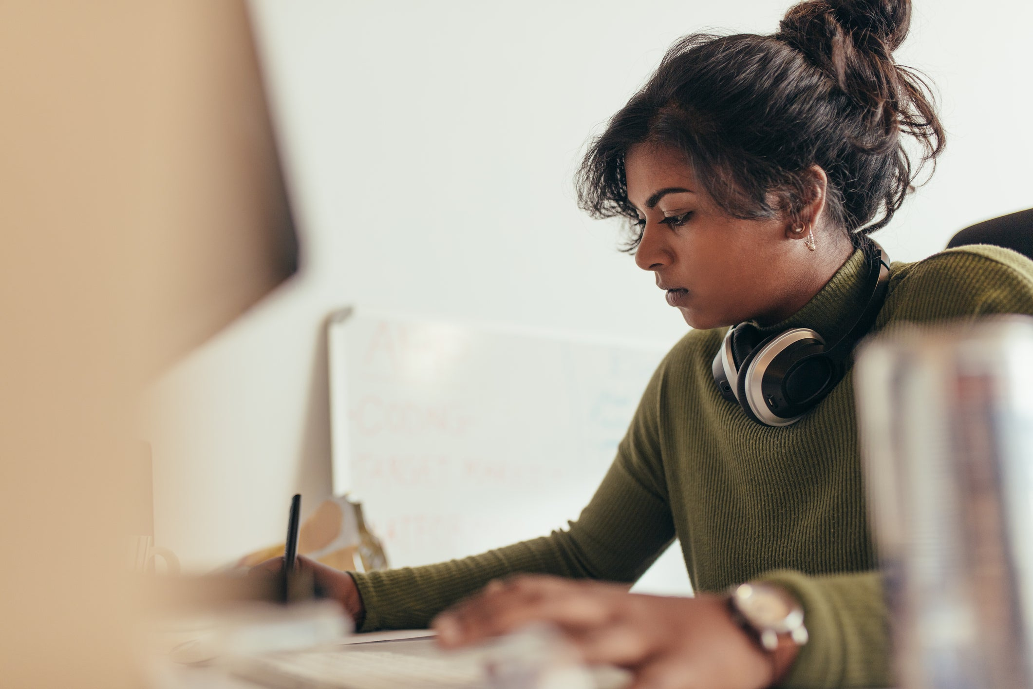 A young woman writing at a desk with headphones hanging around her neck.