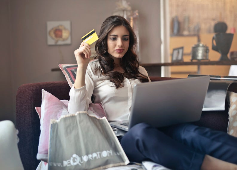 Woman holding credit card with laptop on couch
