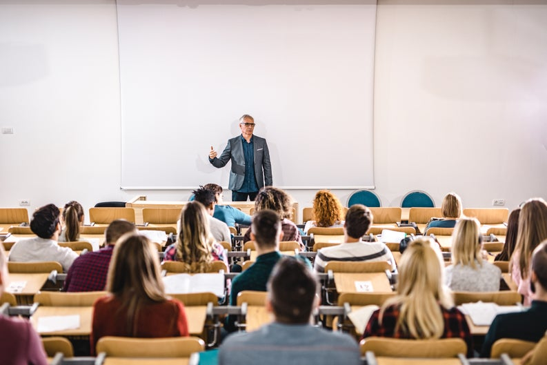A college professor speaking to students seated in a lecture hall.