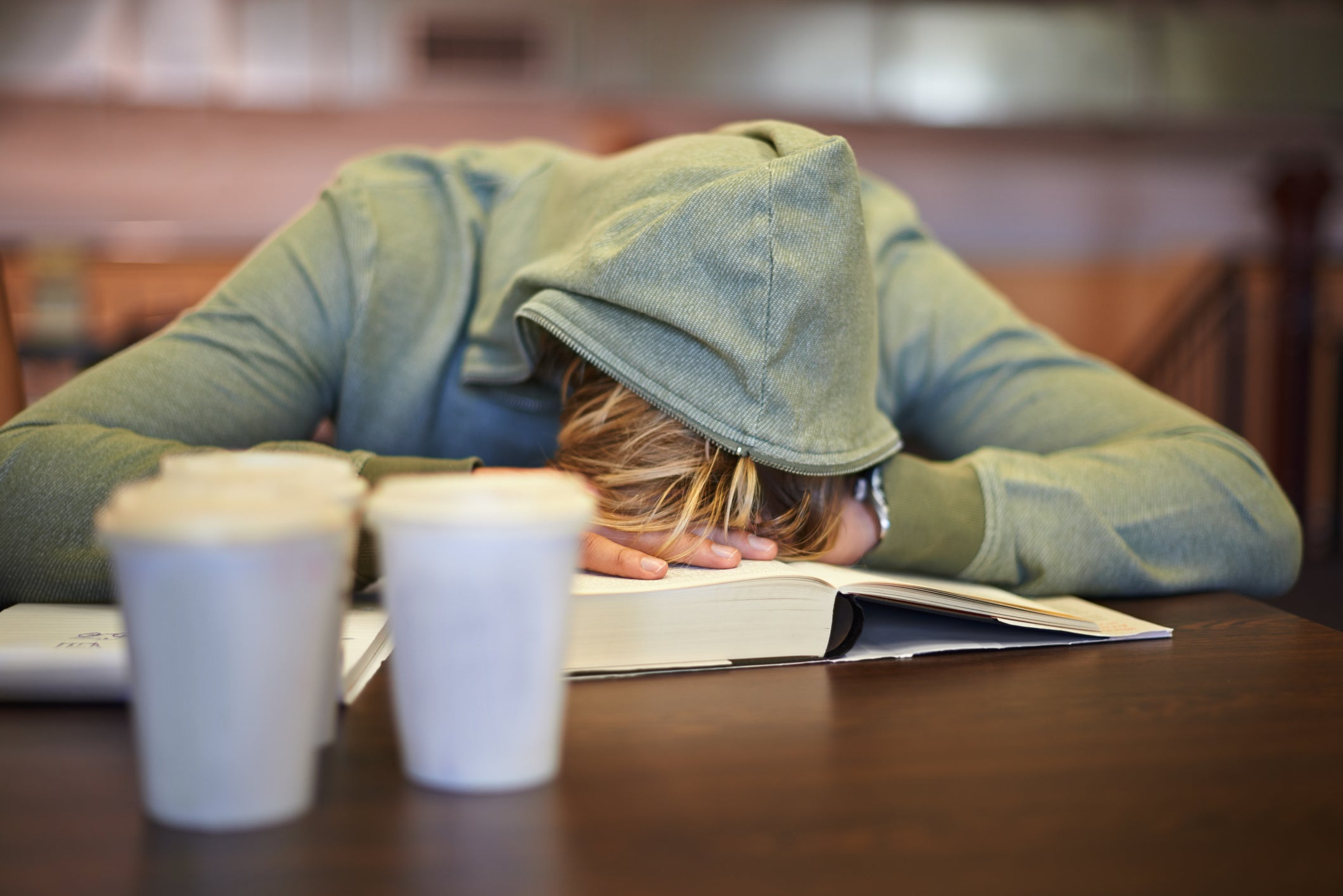 A college student passed out with his head on his textbook.