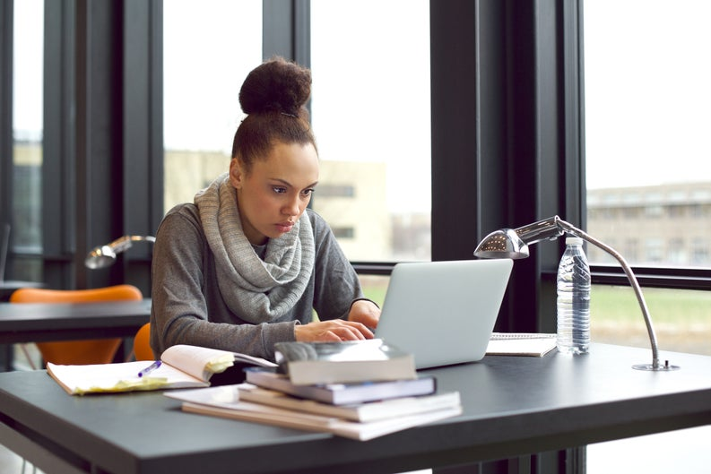 A female college student studying at a desk in the library.
