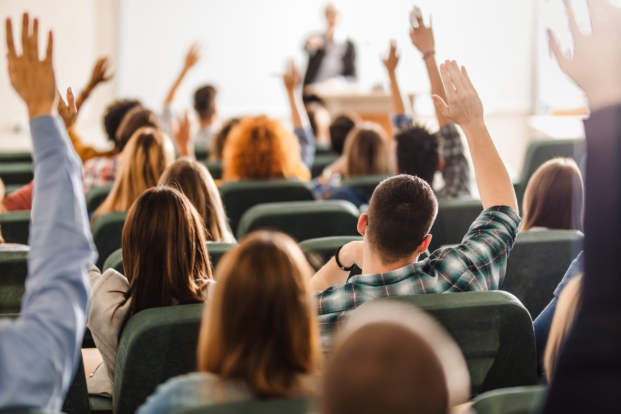 A lecture hall full of college students raising their hands while the professor speaks.