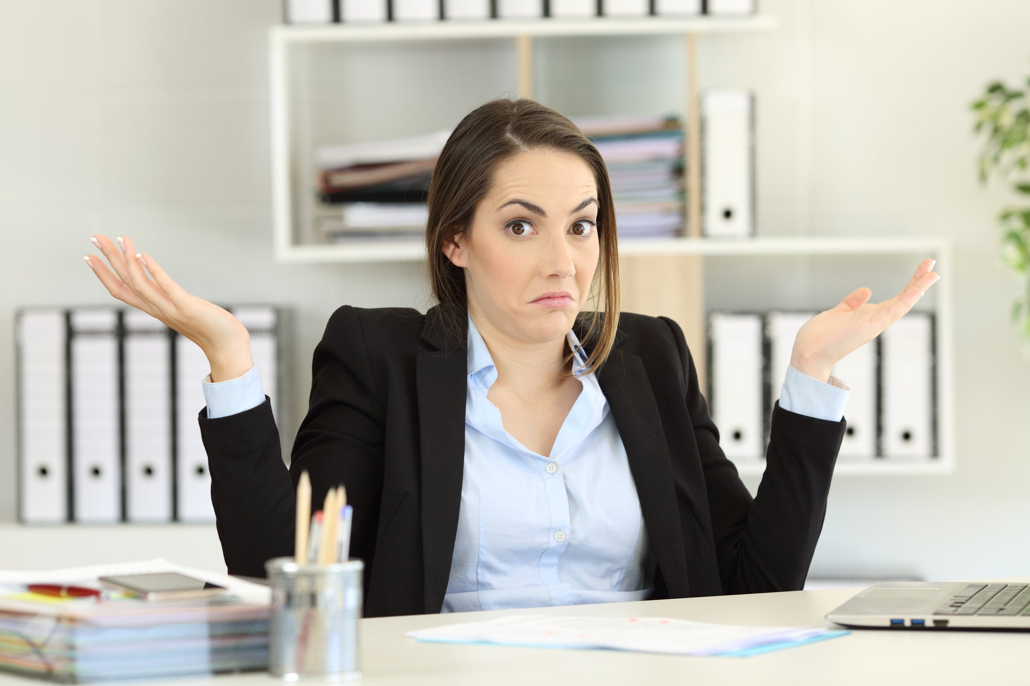 Woman sitting at desk holding her hands up as if confused
