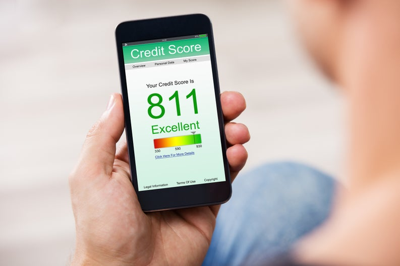 Person holding a cell phone with a screen showing a credit score of 811