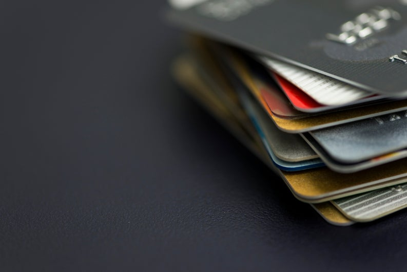 A stack of different credit cards on a dark background.