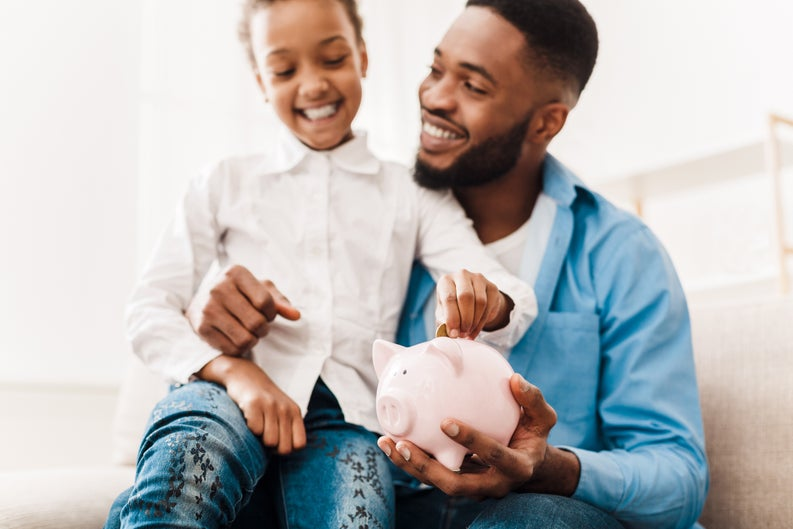 A father and his young daughter put money in a piggy bank.