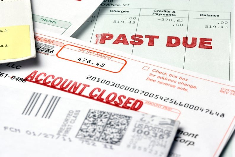 "A stack of bills labeled ""Past Due"" and ""Account Closed"""