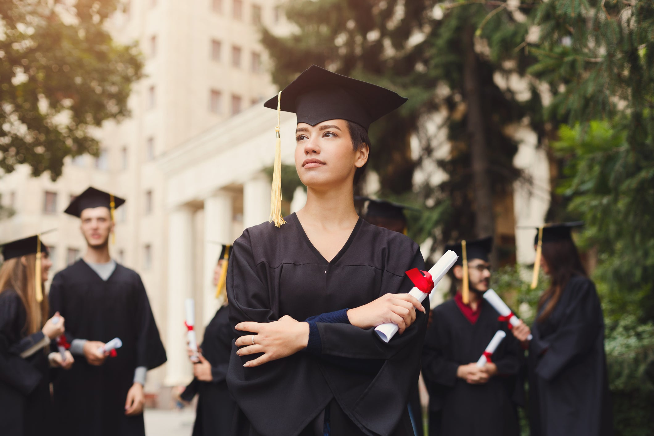 A female college graduate holding her diploma and looking serious.