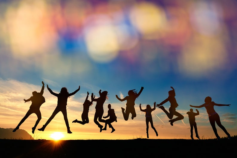 group of people jumping for joy in front of the setting sun.
