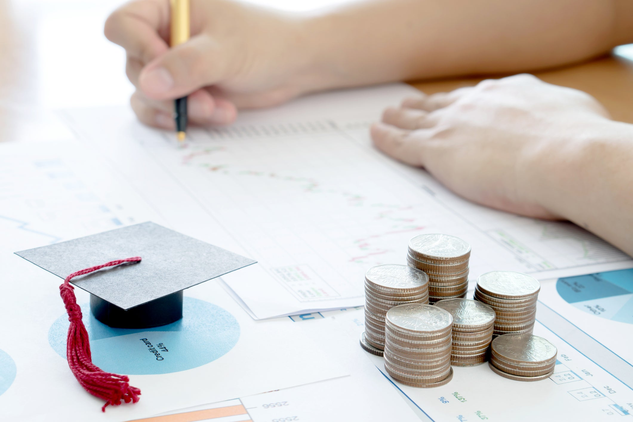hands writing out timeline beside miniature graduation cap and stack of coins