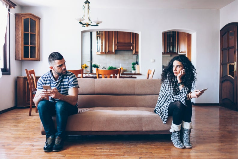 man and woman sitting at opposite ends of a couch and looking upset