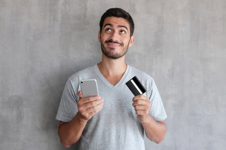 Smiling man in gray shirt holding a cell phone and a credit card