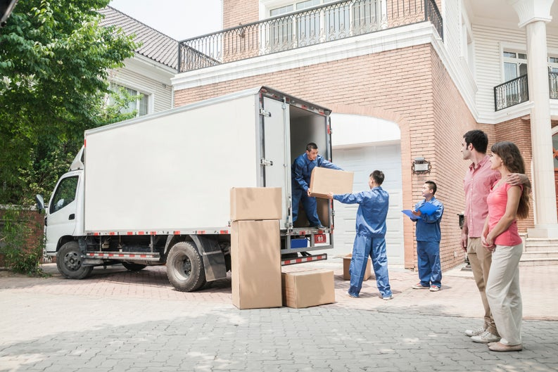 A couple moving into a home with a moving truck.