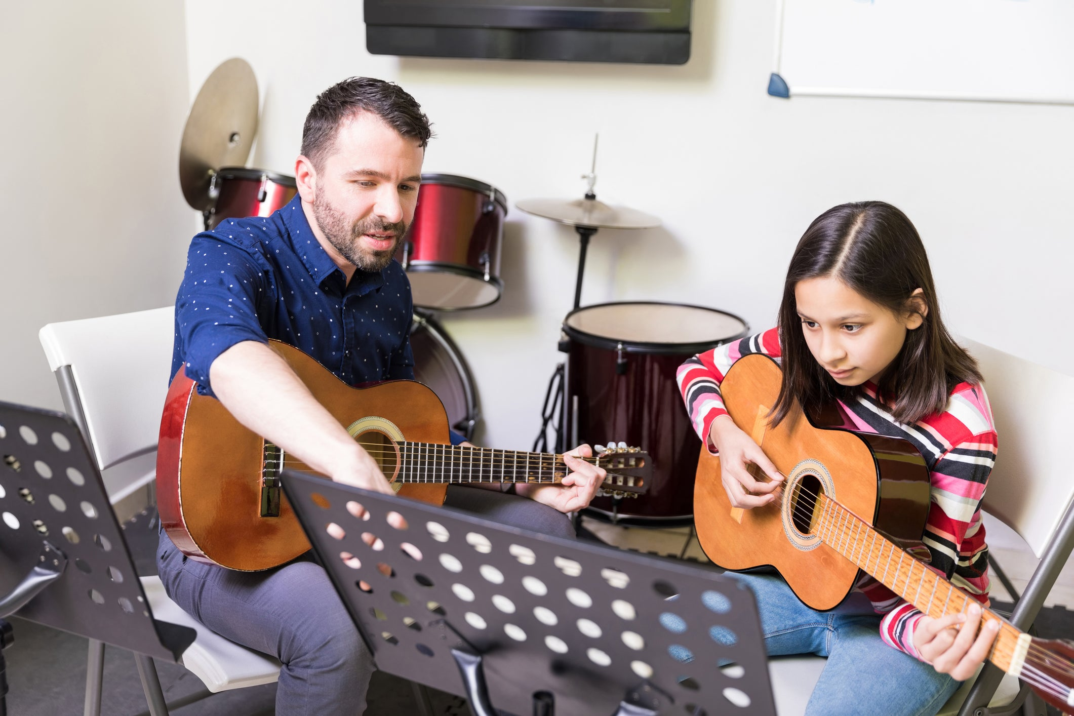A male music teacher and a young student playing the guitar.