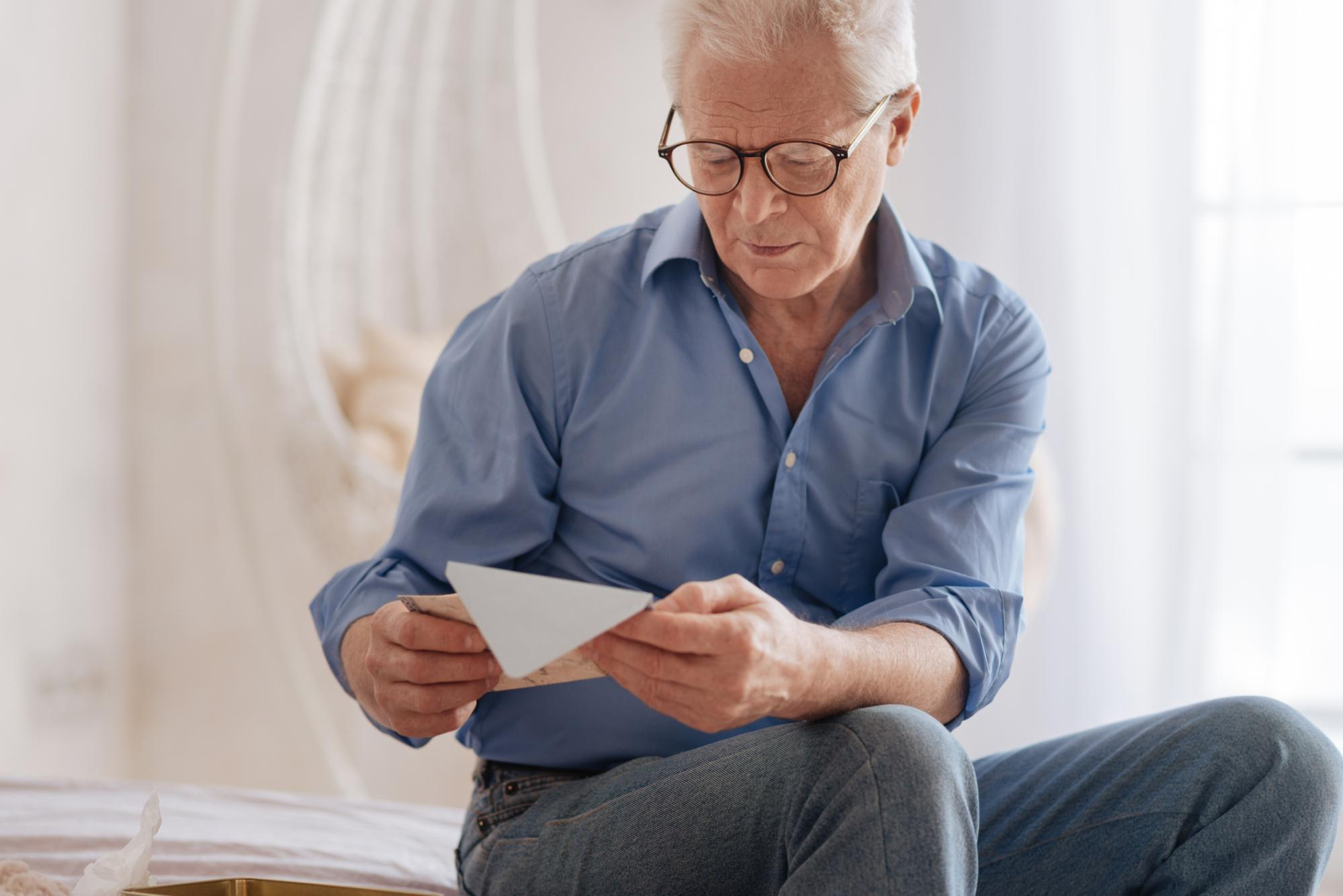 older man looking at envelope