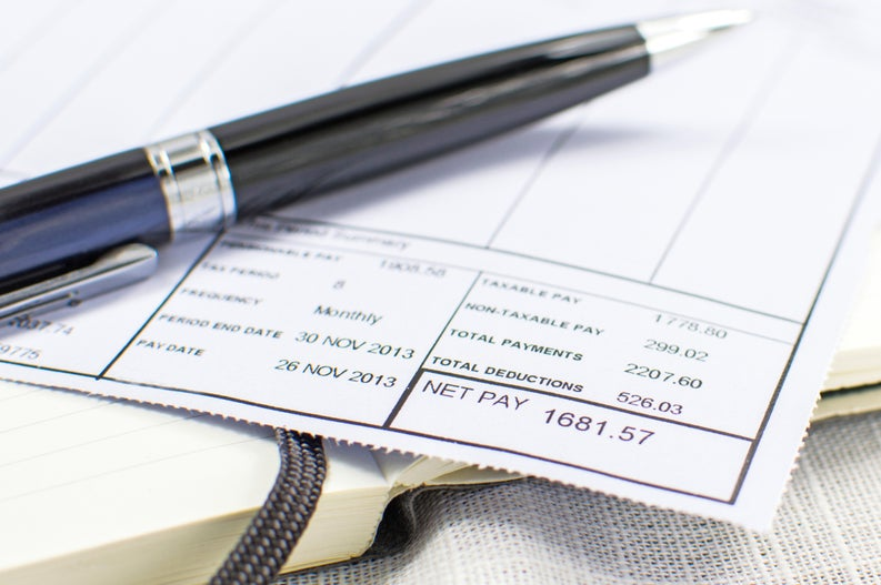 A close up of a paper pay stub and pen.