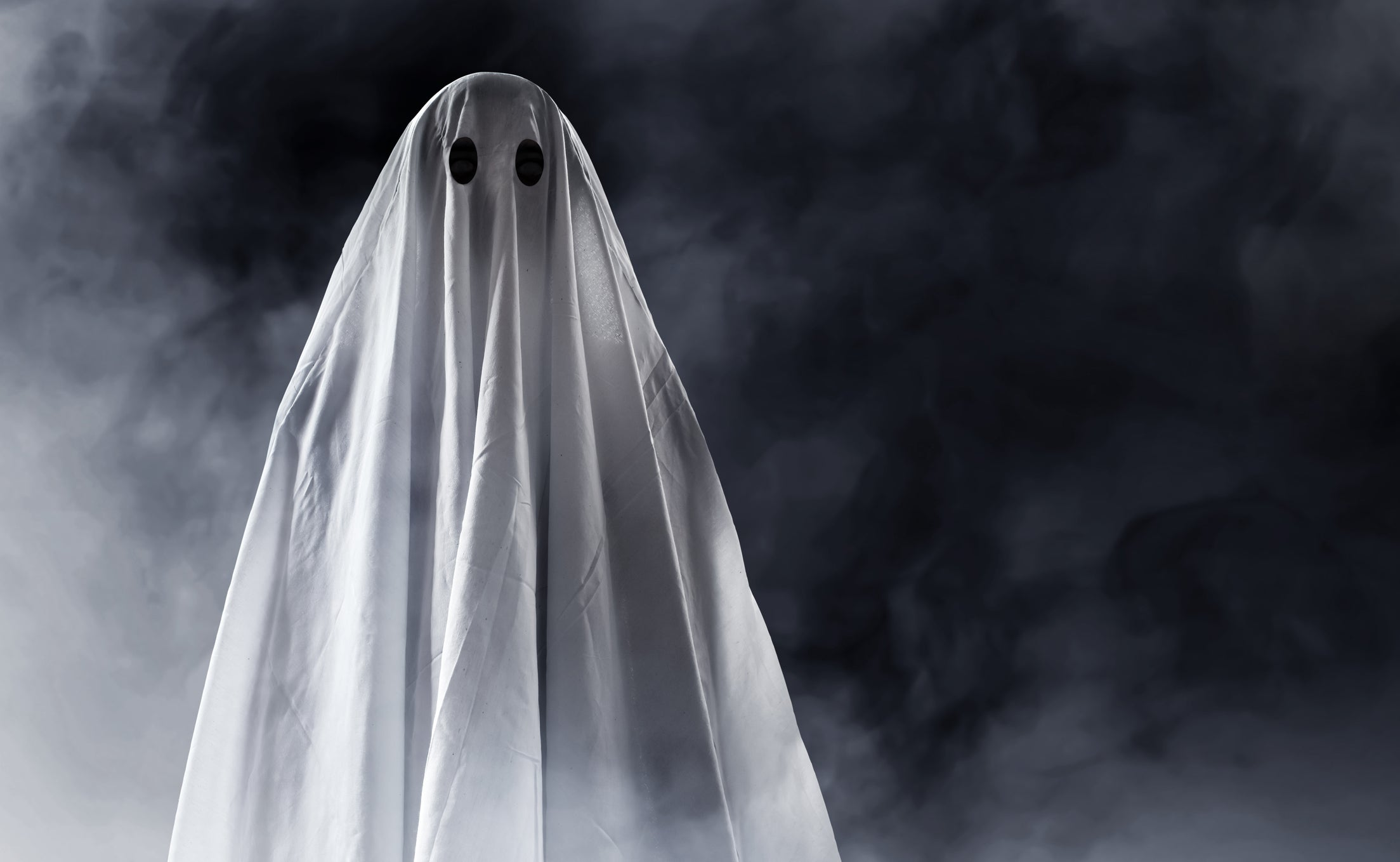 person wearing a sheet as a ghost costume for Halloween.