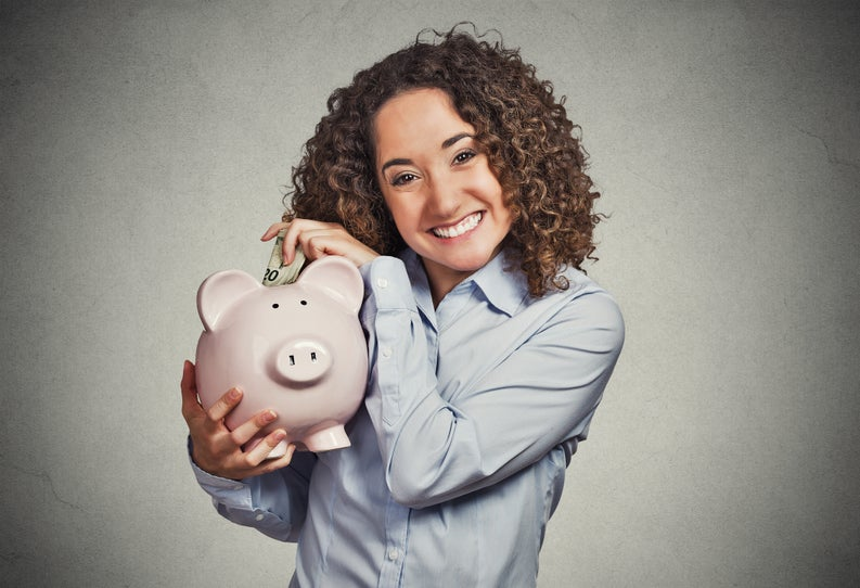 Smiling woman putting money into savings account.